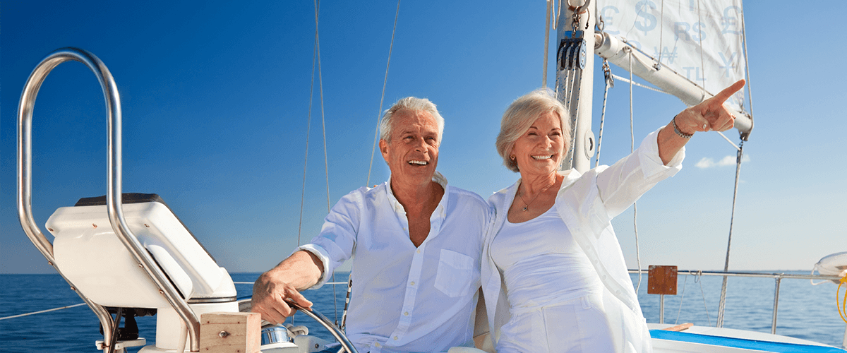 Old couple sailing across ocean pointing to sea
